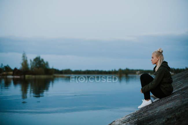 Femme assise sur la rive de la rivière — Photo de stock
