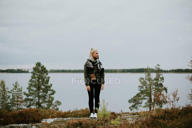Female backpacker standing on mountain hill — Stock Photo