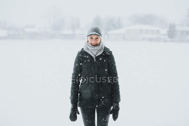 Woman standing in snowy park in countryside — Stock Photo