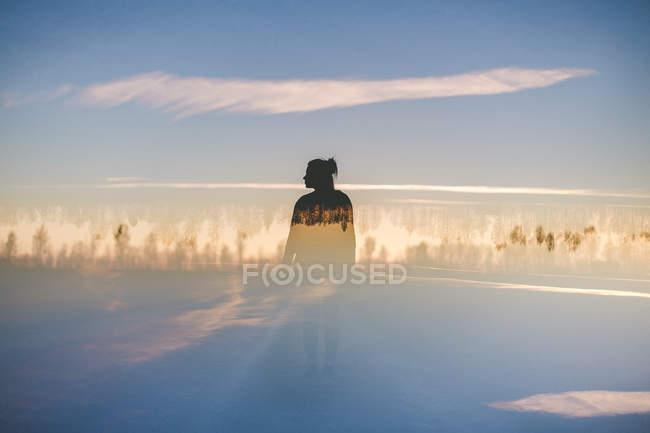 Frau steht bei blauem Himmel im Wald — Stockfoto