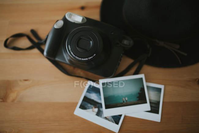 Камера, миттєві фотографії і шапочка на столі — стокове фото