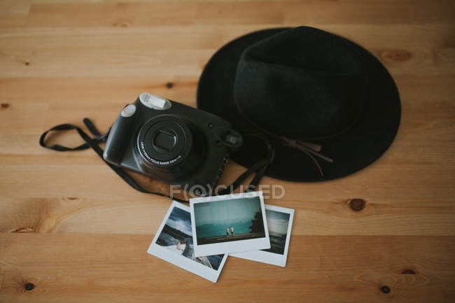 Camera, instant photos and hat on desk — Stock Photo