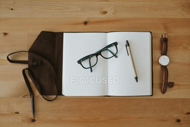 Carnet ouvert avec lunettes et stylo — Photo de stock