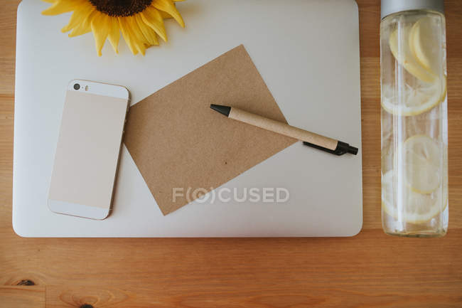 Laptop surface with postcard and pen — Stock Photo