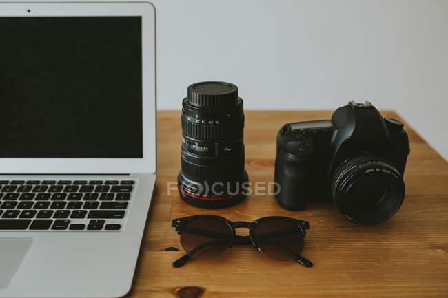 Ноутбук и камера на столешнице — стоковое фото