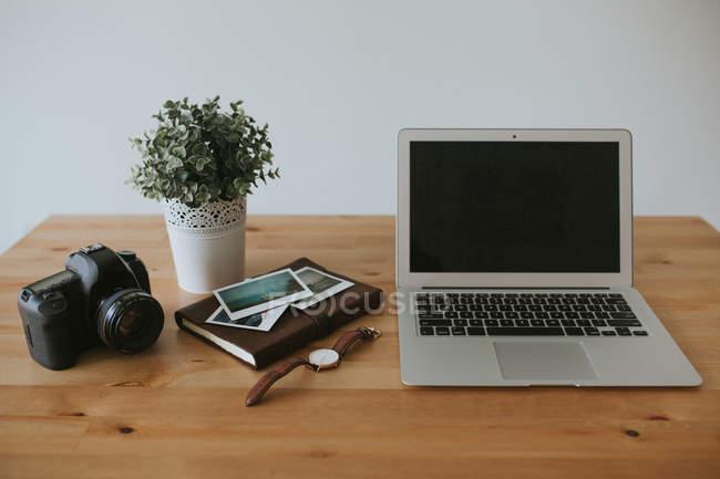 Ordinateur portable et caméra sur table — Photo de stock
