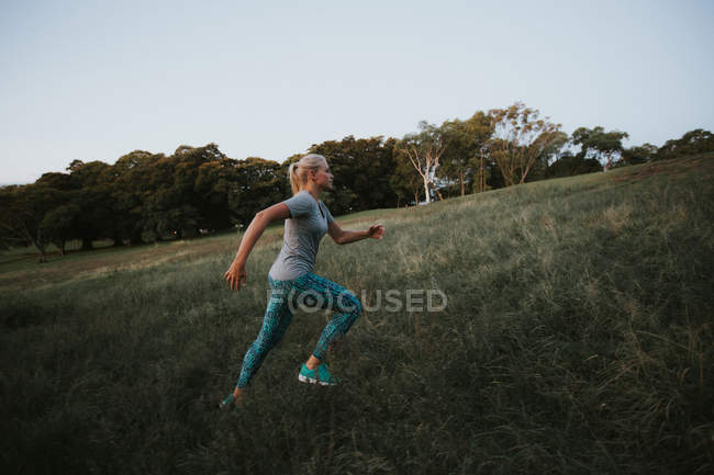 Sporty woman running on hill in park — Stock Photo