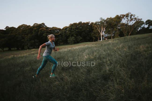 Desportiva mulher correndo colina no parque — Fotografia de Stock