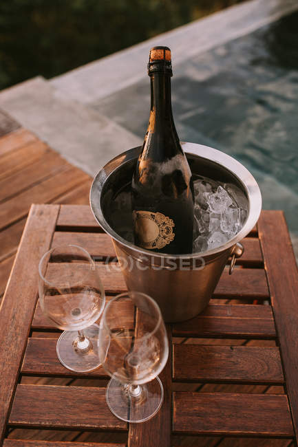 Ice bucket with champagne and two glasses — Stock Photo