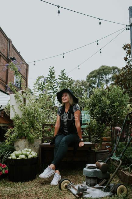 Donna seduta su panchina in giardino — Foto stock