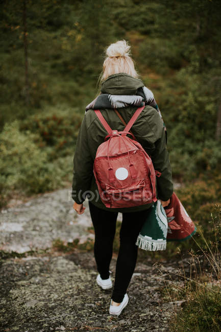 Female backpacker walking on mountain hills — Stock Photo