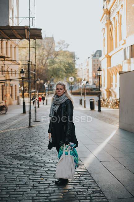 Жінка, стоячи на вулиці з сумками — стокове фото