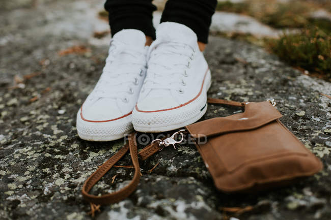 Female sport shoes and handbag on stone — Stock Photo