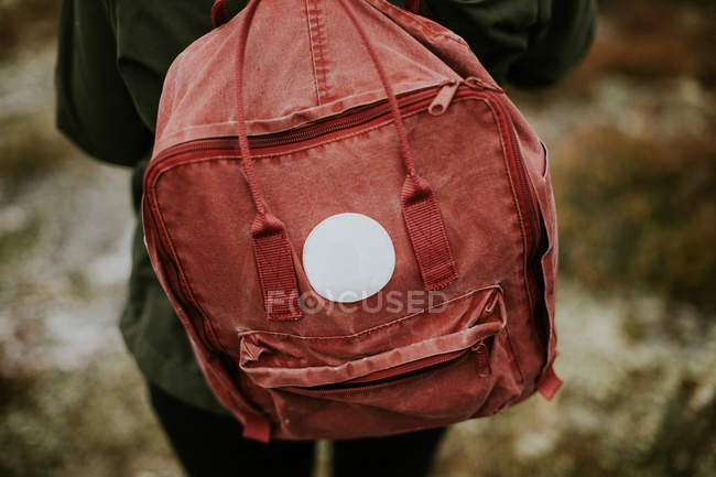 Red backpack on female shoulders — Stock Photo