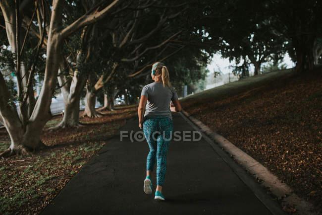 Donna sportiva che corre nel parco cittadino — Foto stock