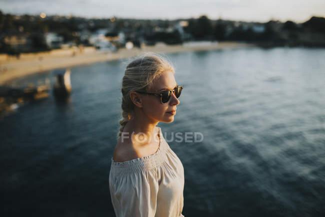 Mulher em óculos de sol olhando para a paisagem marinha — Fotografia de Stock