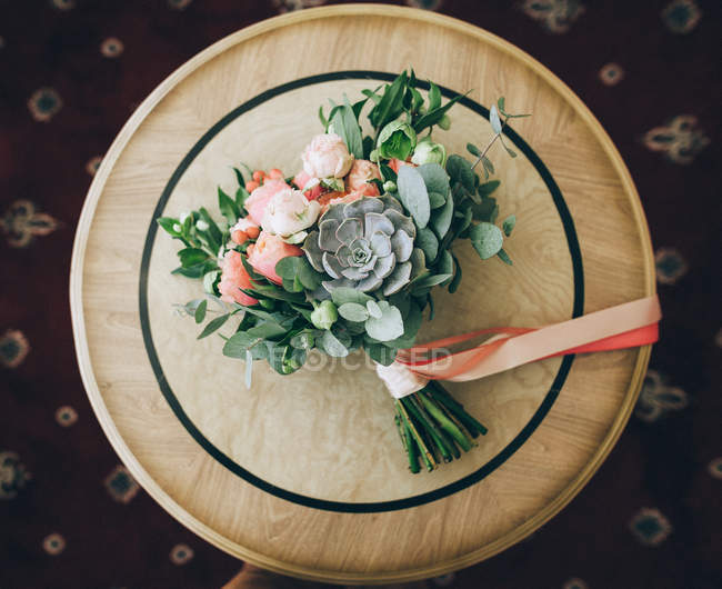 Bridal bouquet of flowers on wooden table — Stock Photo