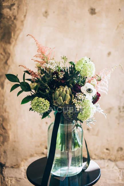 Ramo de flores em vaso colocado na tabela — Fotografia de Stock