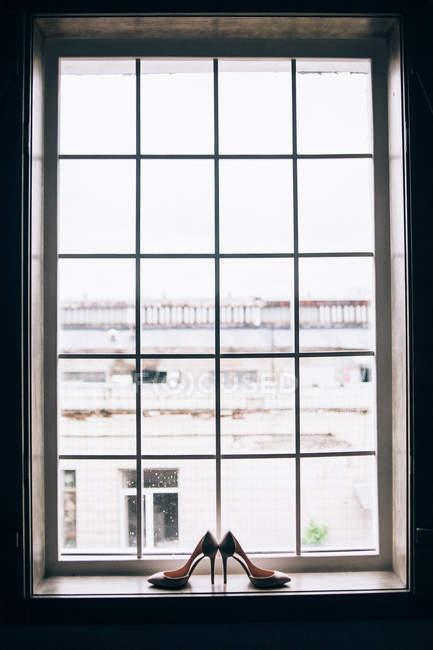 Saltos altos colocados na soleira da janela — Fotografia de Stock