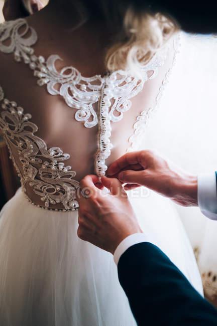 Hands of groom fasten dress — Stock Photo