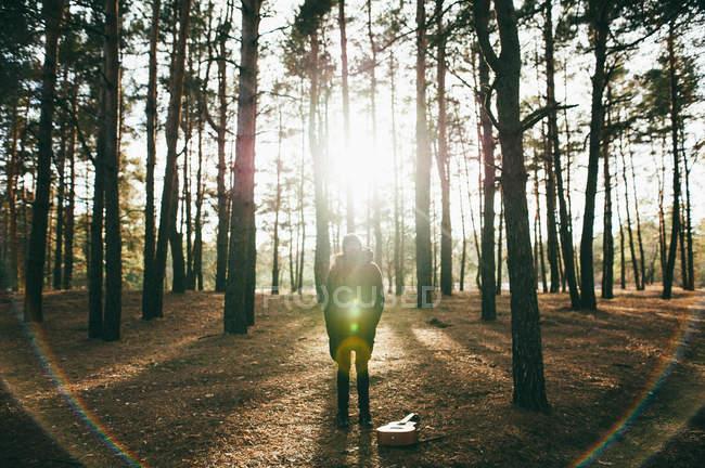 Homme avec guitare au sol debout dans la forêt pendant la saison d'automne — Photo de stock