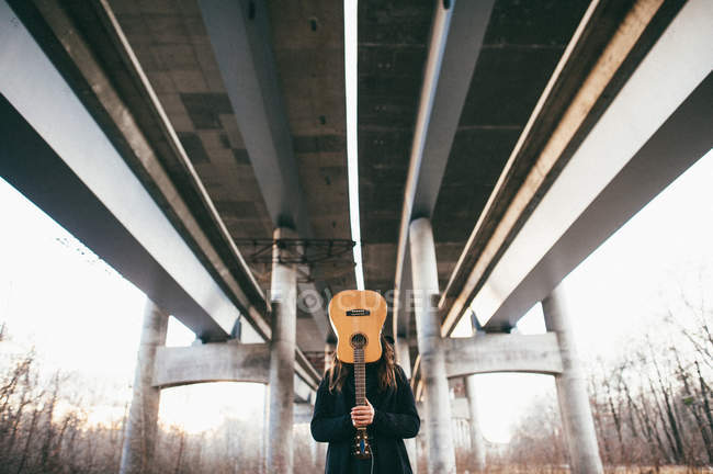 Homme avec guitare sous pont — Photo de stock