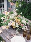 Цветы в вазе на столе на открытом воздухе — стоковое фото
