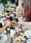 People clincking glasses at setting table — Stock Photo