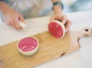 Woman cutting cheese on cutting board — Stock Photo