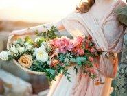 Женщина в платье вуаль Холдинг корзина с розами — стоковое фото