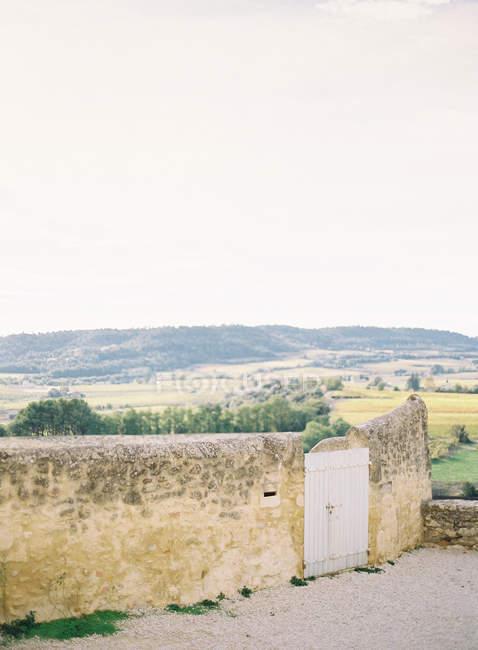 Recinzione in pietra con porta in legno — Foto stock