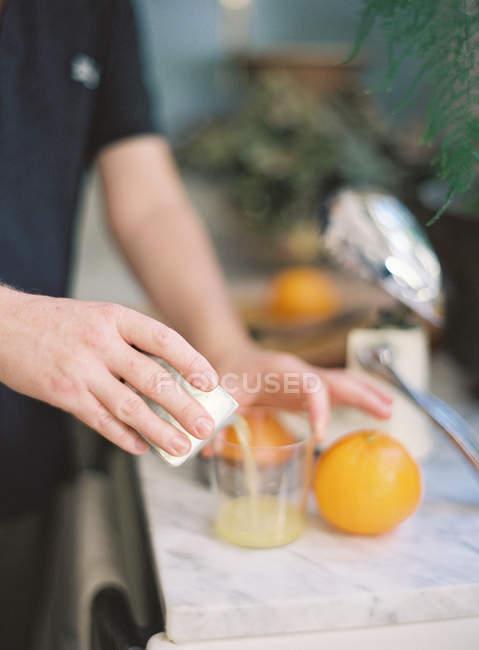 Hands cooking orange juice — Stock Photo