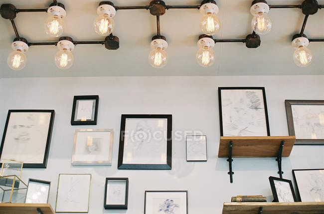 Wall with frames and creative ceiling lamps — Stock Photo
