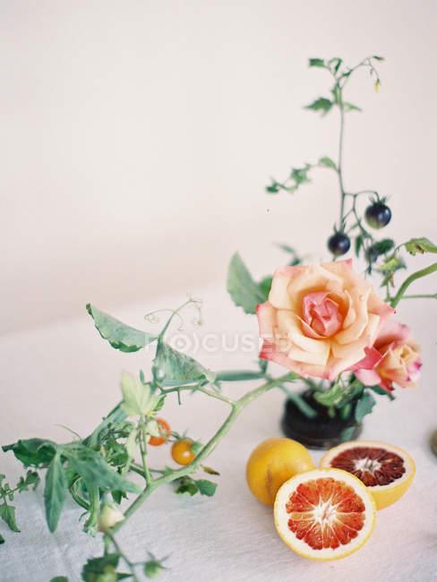 Свежий половинки апельсина с розами — стоковое фото