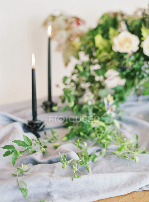 Candles lighting and floral arrangement — Stock Photo