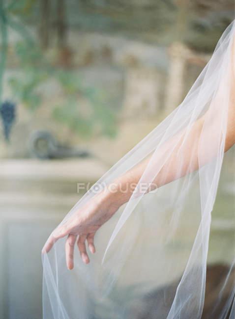 Female hand in bridal veil — Stock Photo