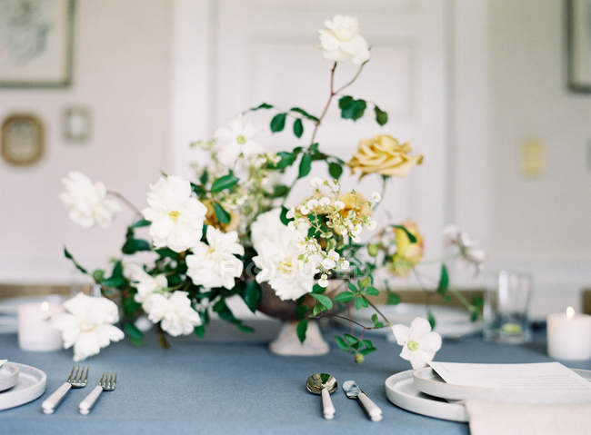 Ramo de flores en la mesa puesta - foto de stock