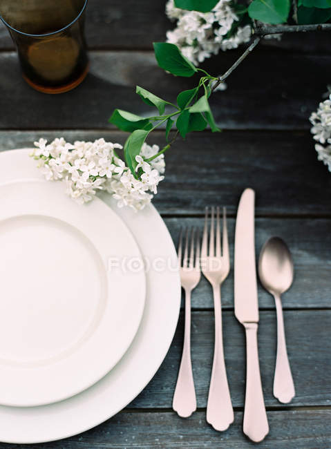 Plates and cutlery on wooden table — Stock Photo