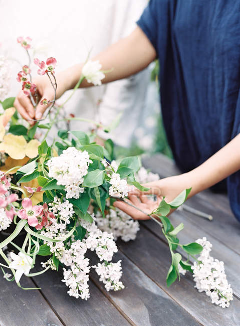 Florists hands setting bouquet of flowers — Stock Photo