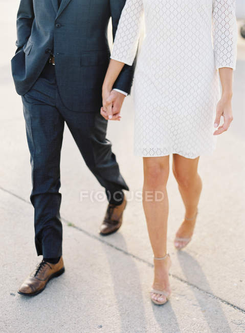 Couple walking hand in hand at airfield — Stock Photo