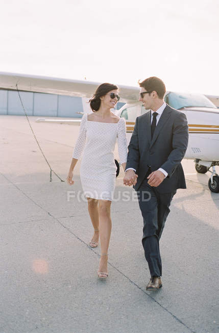 Passionate couple walking at airfield — Stock Photo