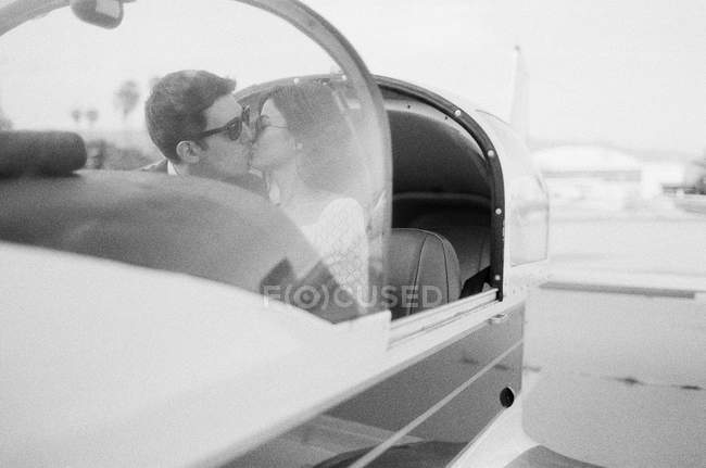 Couple kissing in plane cockpit — Stock Photo