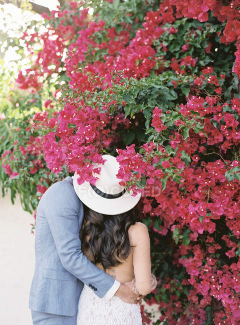 Young couple embracing and smelling flowers — Stock Photo
