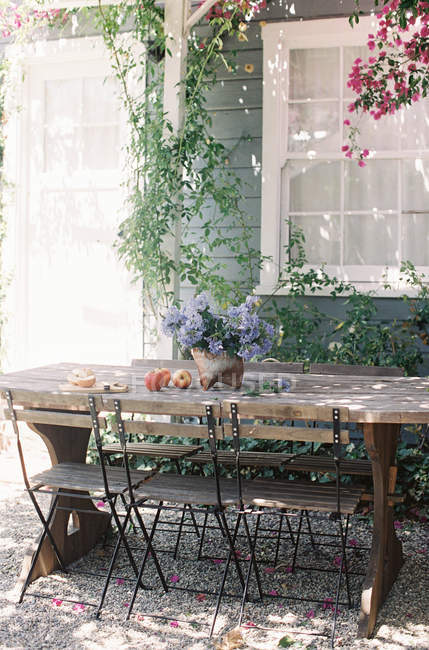 Apples and flowers on rustic wooden table — Stock Photo