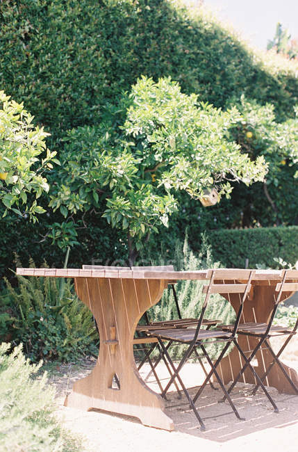 Wooden table with chairs set at garden — Stock Photo