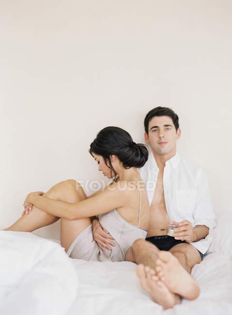 Junges Paar sitzt und entspannt im Bett — Stockfoto