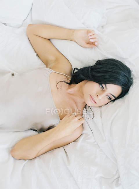 Красивая женщина лежит в постели — стоковое фото
