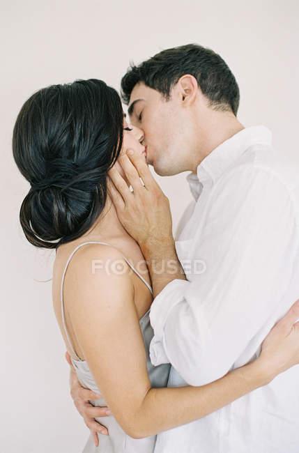 Pareja joven abrazándose y besándose - foto de stock