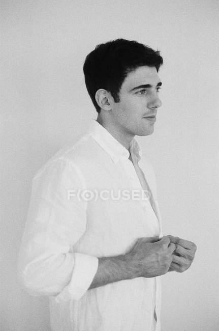 Мужчина расстегивает рубашку и смотрит в сторону — стоковое фото