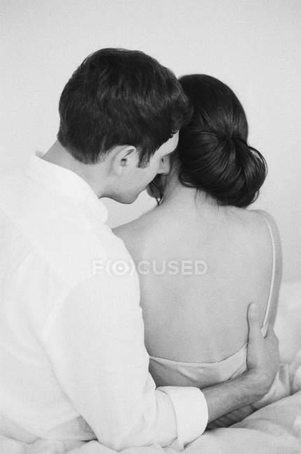 Mann umarmt Frau auf Bett — Stockfoto